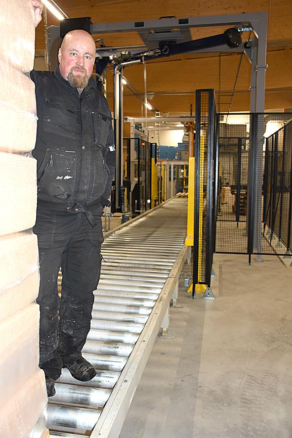 Pasi Pulkkisen takana näkyy hallin mittainen purun käsittely- ja pakkauslinja.