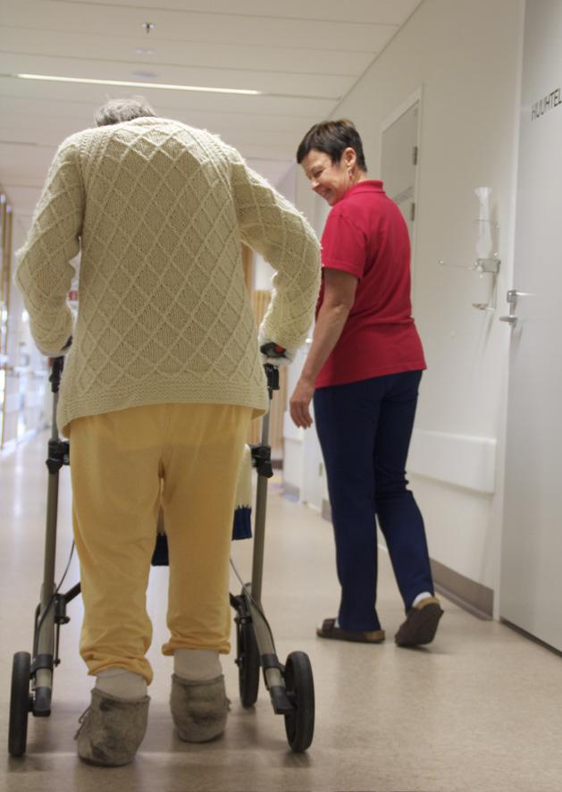 Fysioterapeutti Tarja Karjalainen auttaa potilasta siirtymään ruokasaliin.