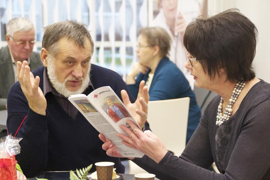 Oleg Tchoumak ja Hannele Mikkanen keskustelevat taiteesta Liperin terveyskeskuksen aulassa.
