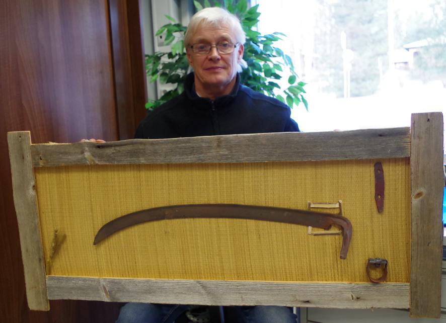 Urpo Hassisella on Postin logolla varustettu viikate.