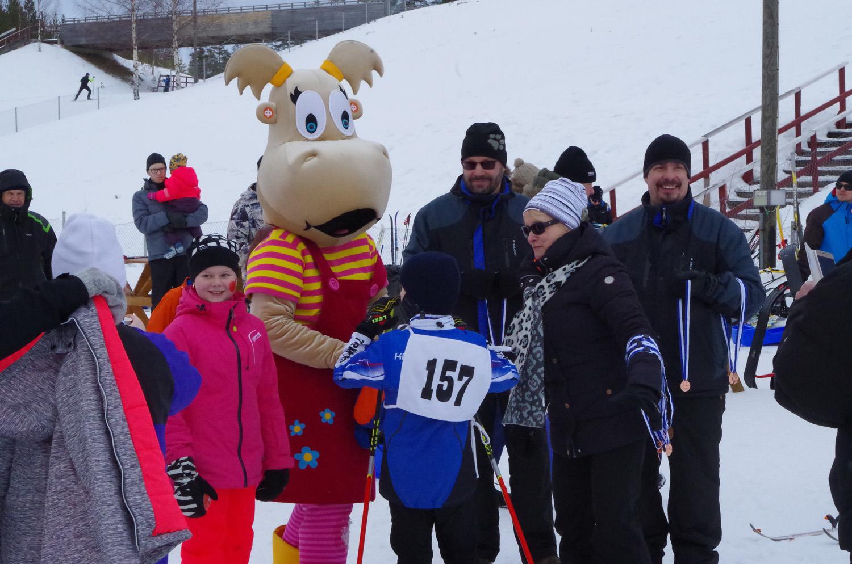 Hanna-Hippo jakoi karkkia kaikille hiihtäjille. Mitalit kilpailijoille ojensivat Jukka Asikainen (Hipon vieressä) ja Harri Kettunen. Kisatyttönä toimi punatakkinen Ada Reijonen.