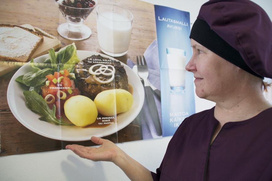 Teija Holopainen näyttää, millainen on lautasmallin mukainen ateria. Asiaa valottava juliste komeilee Liperin koulun ruokalan seinällä.