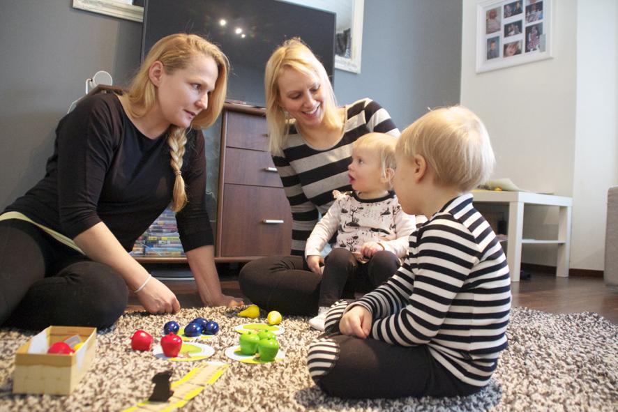 Kati Nylund (vas.) on istahtanut olohuoneen lattialle pelaamaan Laura Haapalaisen ja tämän kahden nuorimman lapsen, 1-vuotiaan Unnan ja 3-vuotiaan Joonaksen kanssa.