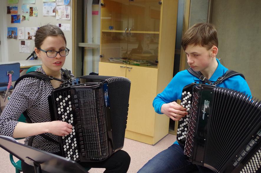 Terhi Sjöblom valottaa Denis Moskvinille harmonikan soittamisen saloja.