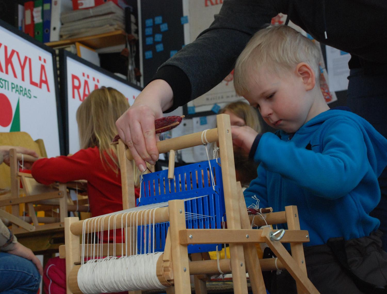 3,5-vuotias Aleksi Pitkänen kokeili kudontapajassa pienen maton tekoa kangaspuilla.