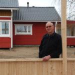 Urho Makkonen myhäilee tyytyväisenä uuden grillikatoksen rakennuksella, sillä kylätalon isompi laajennusprojekti (taustalla) on jo valmistunut.