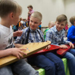 Topias Juntunen, Joona Kinnunen ja Veeti Multanen virittelevät kanteleitaan koko koulun orkesterissa.