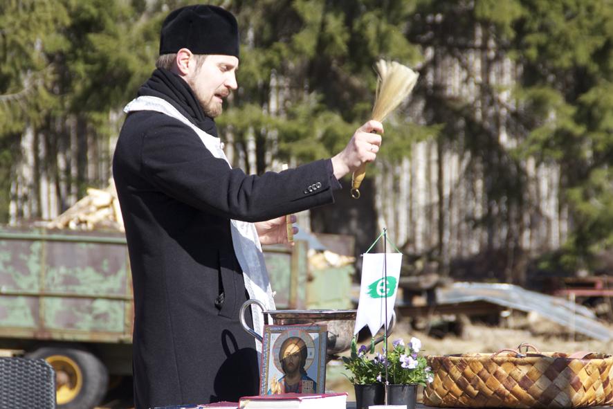 Isä Tuomas pirskottaa pyhitettyä vettä siunattavalle siemenviljalle.