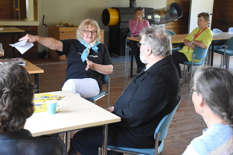 Keskellä istuva Taimi Pulkkinen kertoi muille värikkäästi kylän elämästä sotien jälkeen.