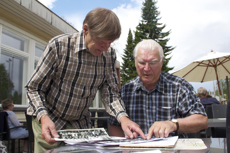 Veikko Pietarinen ja Kalevi Leppänen tarkastelevat vanhoja luokkakuvia ja yrittävät tunnistaa entisiä koulutovereitaan.