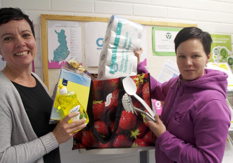 Minna Turunen (vas.) ja Minna Ikonen kurkistavat, mitä seurakunnan lahjoituskassi pitää sisällään.