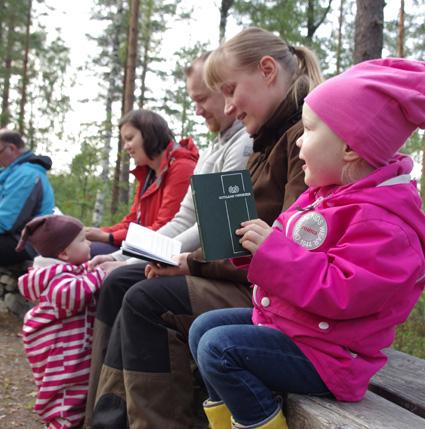 Eveliina Heinonen luritteli sotilaan virsikirjan lauluja metsäkirkossa. Taustalla äiti Varpu Kuutti sekä sisko Viivi ja isä Antti Heinonen.