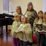 Liperin seurakunnan lapsi- ja nuorisokuoro kantaa nyt nimeä Lehmus. Keskellä eturivissä Enni Heikkinen kukka hiuksissaan.