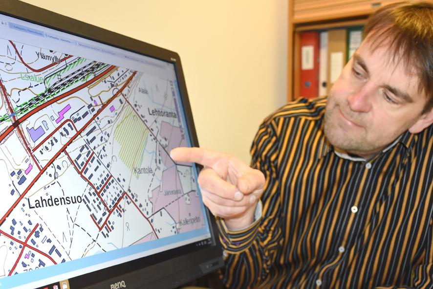 Tommi Hirvonen näyttää kartalta Lahdensuon ja Lautasuon alueita, joille on tulossa tonttitarjontaa.