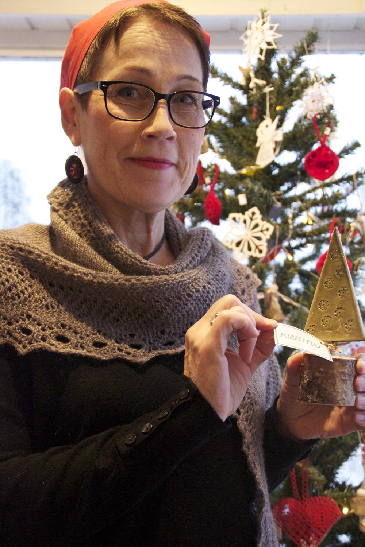 Heidi Mononen esittelee tekemäänsä joulukuusta Lipin puna-valkoiseksi koristellun kuusen edessä.