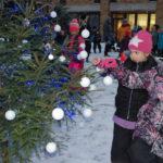Eskarilainen Kiira Pitko ja ekaluokkalainen Hanna Vesanen ripustivat valkoiset pallot kuusen oksille.