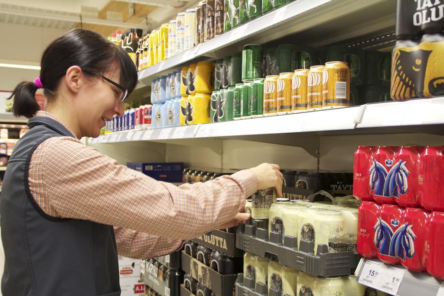 Heidi Toropainen järjestelee alkoholijuomahyllyä K-market Neliapilassa Liperin kirkonkylällä.