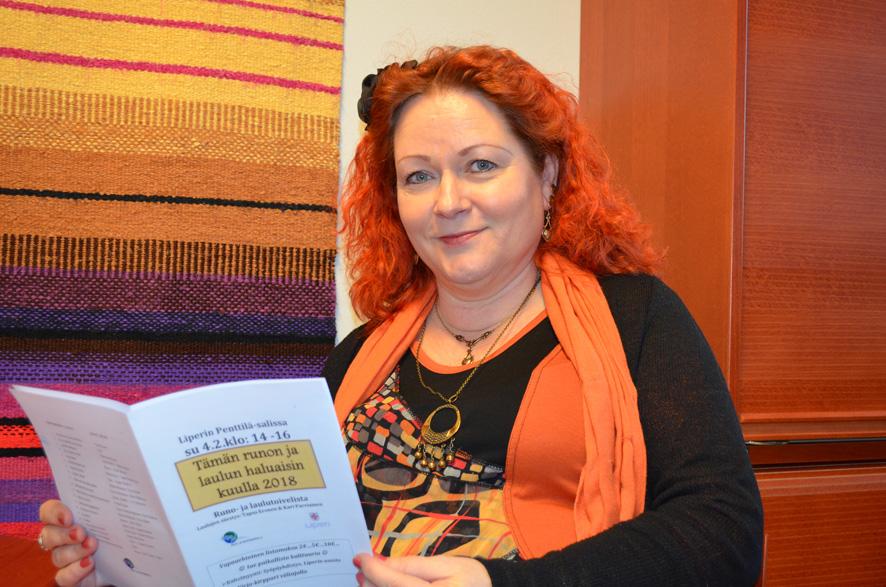 Virpi Eronen esittelee runotoivetilaisuuden käsiohjelmaa.