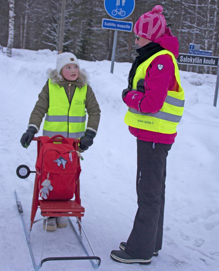 Viidesluokkalainen Sini Reinikainen potkukelkkailee kouluun. Tiina Karvinen antaa neidille kiitosta huomioliivin käytöstä.
