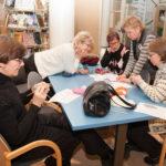 Sanni Vestman (edessä vasemmalla), Pirjo Viitala, Rauni Vilkman, kirjastovirkailija Heli Sallinen ja Saara Jääskeläinen miettivät yhdessä silmukoiden paikkaa.