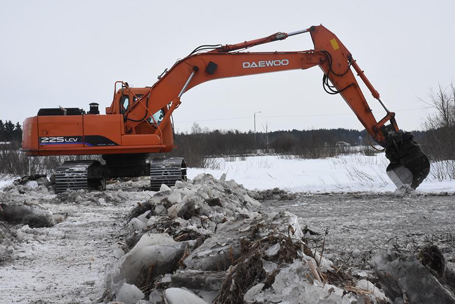 Jarkko Lankisen kaivinkone eteni jäistä kasattua tietä pitkin ja poisti kasvustoa vesikanavien tieltä.