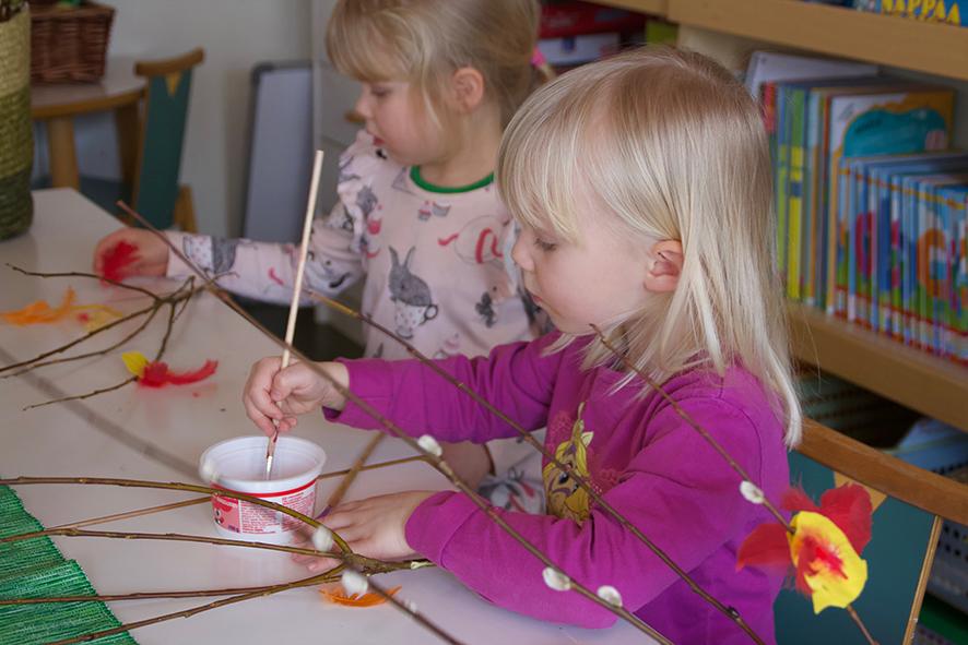Matilda (vas.) ja Vilma koristelevat virpomavitsojaan keltaisin, punasiipisin linnuin.