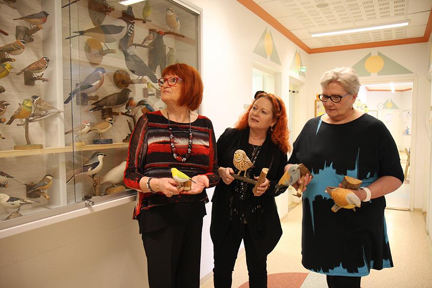 Pirjo Kettunen (vasemmalla) ja Eila Pesonen (oikealla) kävivät lahjoittamassa isänsä Reino Kettusen tekemät puulinnut Liperin koulun opetuskäyttöön. Apulaisrehtori Virpi Eronen sai kunnian ottaa linnut vastaan.