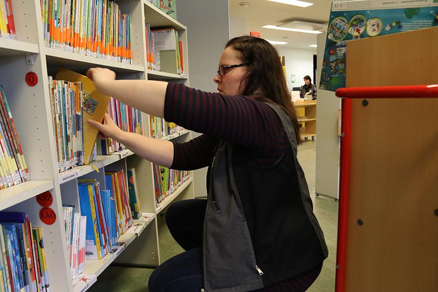 Ylämyllyn kirjastossa kirjat istuvat tiiviisti. Kirjastonjohtajan sijainen Kirsi Nieminen järjestää kuvakirjoja samalla, kun Ulla Kröger palvelee tiskillä asiakkaita.